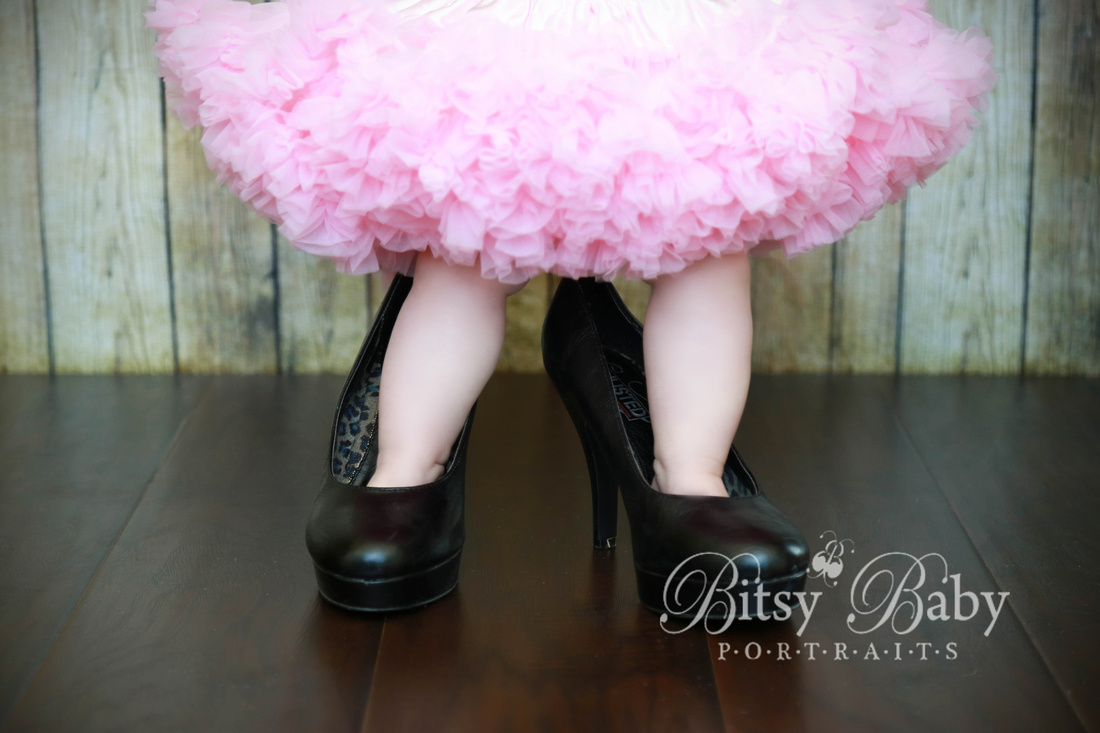 Baby in a pink tutu standing in mommy's shoes, 6-month old