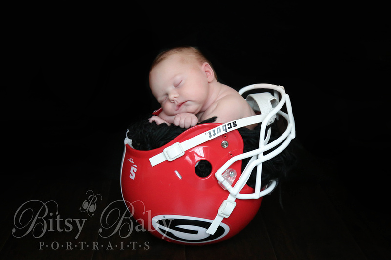 Baby in a uga football helmet